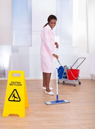 Full length of African American female housekeeper cleaning floor in hotel