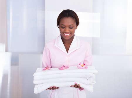 Sonriendo ama de casa mujer joven que lleva las toallas en el hotel Foto de archivo