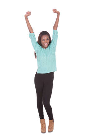 Full length portrait of excited young woman with arms raised standing against white background photo