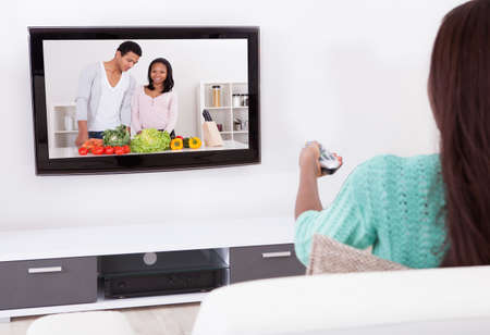sofa television: Side view of young woman watching TV in living room Stock Photo