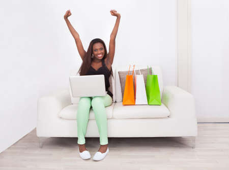 buy: Full length portrait of excited woman shopping online at home Stock Photo
