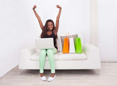 Volledige lengte portret van opgewonden vrouw thuis online winkelen Stockfoto