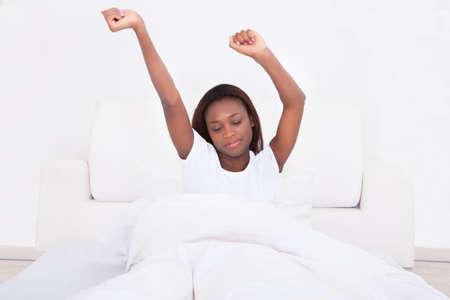 puños cerrados: Joven mujer se extiende en la cama en su casa