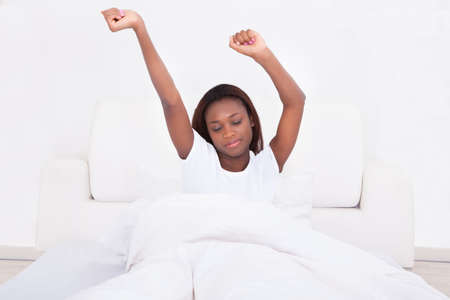 Young woman stretching in bed at home photo