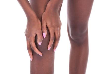 Mediana do Africano mulher americana que sofre de dor no joelho contra um fundo branco