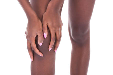 on hands and knees: Midsection of African American woman suffering from knee pain against white background