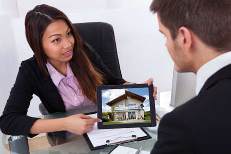 Businesswoman showing digital tablet to male colleague with house photo photo