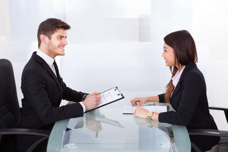 Side view of business colleagues with clipboards discussing at desk in office