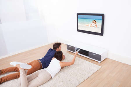 Young couple watching TV while lying on rug at home photo