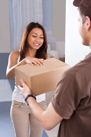 delivery man: Smiling young woman receiving courier from delivery man at home Stock Photo