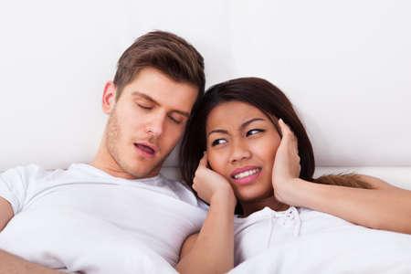 pareja durmiendo: Mujer joven irritada que cubre las orejas mientras mira a roncar hombre en la cama en su casa