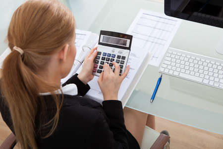Portrait Of Happy Young Businesswoman Sitting At Desk Calculating Finance photo