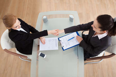 Portrait Of Two Happy Businesswoman Having Handshake In Office photo