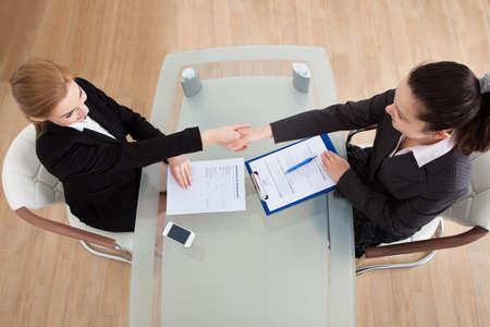 Portret van twee gelukkige Onderneemster die Handdruk In Office