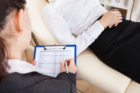 Close-up Of Young Female Psychiatrist Writing On Clipboard Stock Photo - 27241535