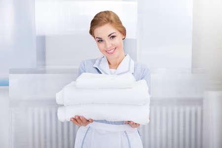 empleadas domesticas: Retrato de la criada joven feliz celebraci�n de Toallas Foto de archivo