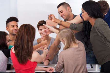piling: Group of university students piling fists at desk in classroom