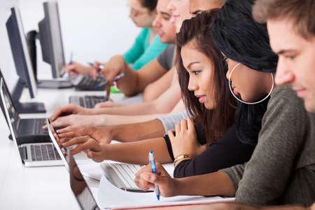 estudiantes: Las estudiantes universitarios que usan la computadora portátil en el escritorio en la clase de informática