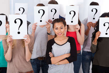 Portrait of beautiful college student surrounded by classmates holding question mark signs in classroom photo