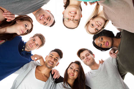 huddle: Low angle portrait of confident college students forming huddle over white background Stock Photo