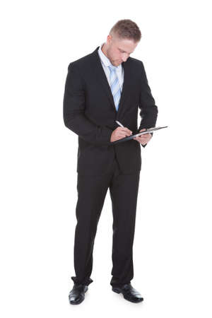 businessman standing: Businessman standing writing on a handheld clipboard as he takes notes during a quality control check or survey  isolated on white