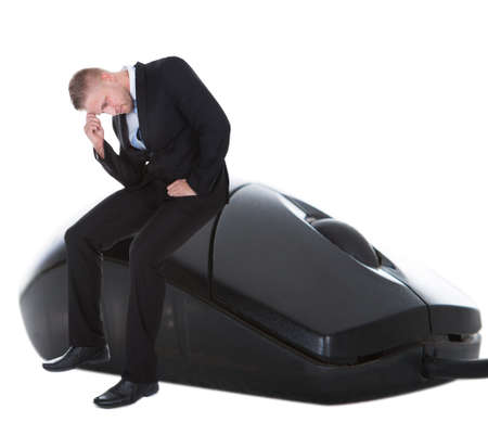 slumped: Worried businessman sitting on a computer mouse with his head in his hand in despair  conceptual of online communication and e-commerce