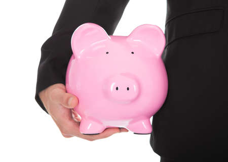 thrift box: Closeup of businessman in a suit standing holding a pink ceramic piggy bank under his arm as he smiles at the camera in a conceptual financial  savings mad investment image  isolated on white