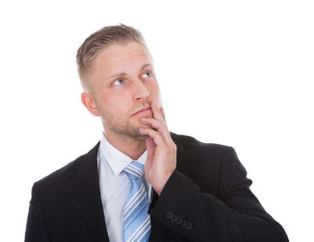 quandary: Businessman standing deep in thought with his hand to his chin looking up into the air with a look of contemplation isolated on white with copyspace