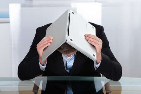 downhearted: Depressed businessman sitting at a reflective table hiding under his laptop as he holds it open over his bowed head Stock Photo