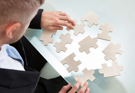 Businessman with a jigsaw puzzle spread out on his desk trying to match the pieces in a concept of problem solving and meeting business challenges  over the shoulder view from above Stock Photo