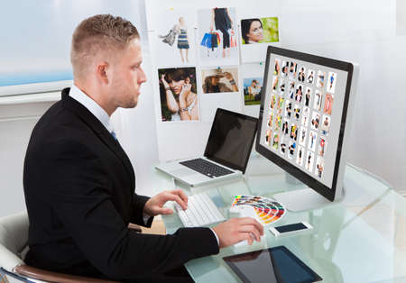 Businessman sitting at his desk in front of a large screen monitor editing photographs photo