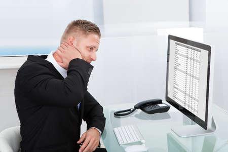 実業家の混乱や剛性を緩和するために彼の首をこすりデスクトップ モニターに関するオンラインのスプレッドシートを勉強 写真素材