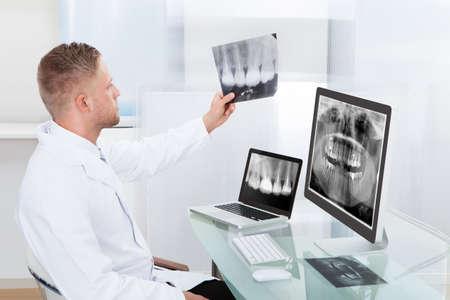 dientes con caries: Doctor o radiólogo que mira una radiografía en línea que presenta un monitor de escritorio como lo hace un diagnóstico o cheques pronóstico