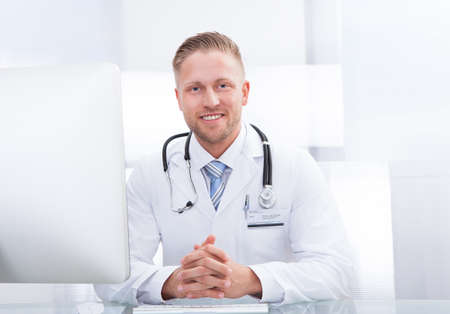Smiling doctor or consultant sitting at a desk with his stethoscope around his neck looking at the camera photo