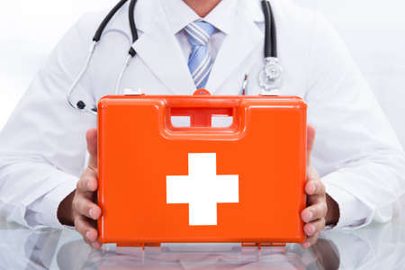 response: Smiling doctor or paramedic in a white lab coat with a stethoscope around his neck holding a red box containing a first aid kit Stock Photo