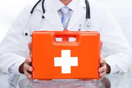 Sonriendo médico o paramédico en una bata blanca de laboratorio con un estetoscopio alrededor de su cuello que sostiene un cuadro rojo que contiene un botiquín de primeros auxilios Foto de archivo