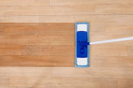 Bovenaanzicht van een moderne stijl spons mop wordt gebruikt voor het reinigen van een houten vloer met copyspace
