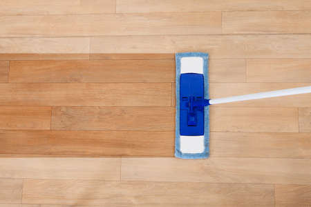 wood floor: Overhead view of a modern sponge style mop being used for cleaning a wooden floor with copyspace Stock Photo