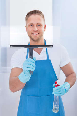 service occupation: Male janitor using a squeegee to clean a window in an office wearing an apron and gloves as he works