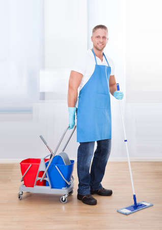 custodian: Janitor cleaning wooden floors with a mop and a cart with two buckets for the disinfectant and water pausing to smile at the camera as he goes about his work in an office building