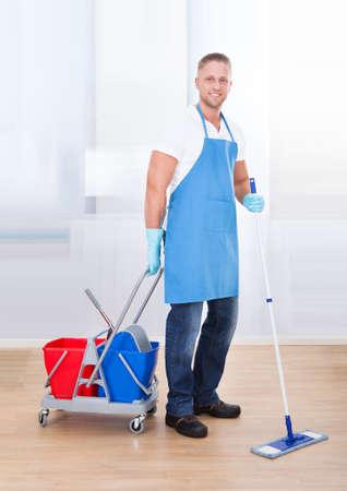 desinfectante: Janitor limpieza de suelos de madera con un trapeador y un carro con dos cubos para el desinfectante y la pausa del agua para sonre�r a la c�mara como �l va sobre su trabajo en un edificio de oficinas