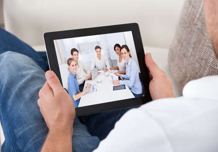 handheld: Businessman on a video call chatting to colleagues in a meeting visible on the screen of his tablet