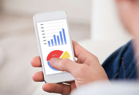 proportion: Man looking at graphs on his smartphone as he relaxes in comfort at home  view of the screen in his hand Stock Photo