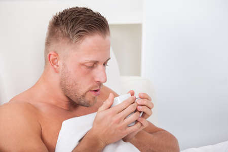recuperating: Man lying in bed propped up against the pillows drinking a cup of hot tea