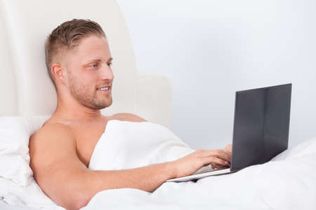 man sitting up in bed against the pillows working on a laptop computer smiling as he