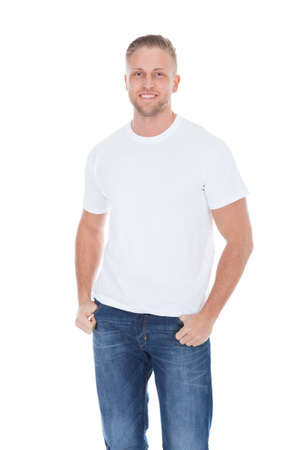 hooked: Friendly relaxed young man with a beard standing with his thumbs hooked in the pockets of his jeans smiling at the camera  isolated on white