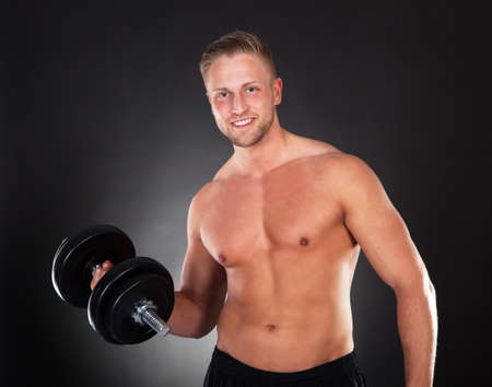 Young man with a muscular physique smiling while working out lifting weights in a gym in a health and fitness concept photo