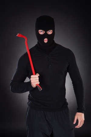 threateningly: Masked thug or criminal with a crowbar raising it threateningly as he advances out of the darkness  conceptual of crime and violence