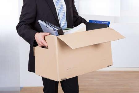 Buik van zakenman verhuizen met kartonnen doos uit zijn ambt Stockfoto