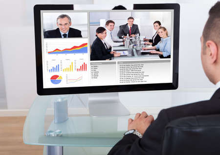 webcam: Rear view of businessman video conferencing with team on computer in office Stock Photo